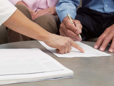 Claims adjuster pointing at document --- Image by © Monalyn Gracia/Corbis